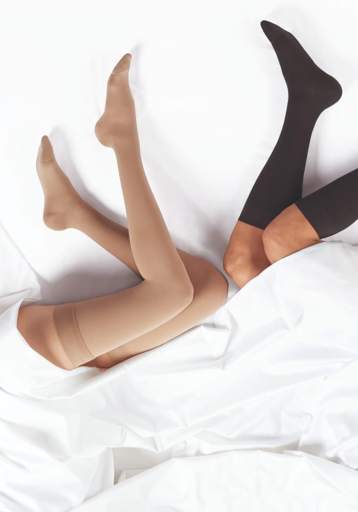 31b0916ce31a89 Damskie i męskie nogi leżące na białej pościeli , ubrane w pończochy i  podkolanówki na żylaki